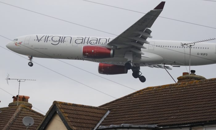 An Airbus A330-300 of Virgin Atlantic on final approach to landing skims over the rooftops of nearby houses at Heathrow Airport in London, on Oct. 25, 2016. (AP Photo/Frank Augstein)