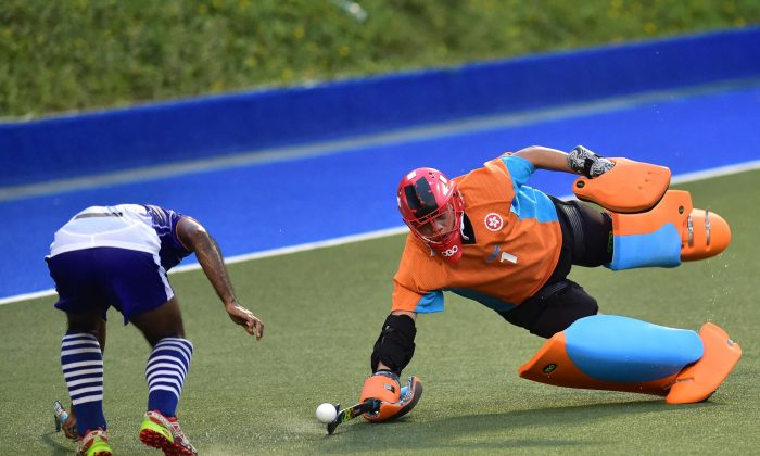 KNS Goalie Chan Hou Fung dives to stop a shot from an SSSC attacker , while his teammate backs up, during their premier division match at King's Park on Sunday Oct 23. (Bill Cox/Epoch Times)