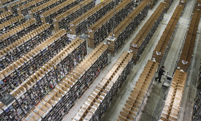 A worker pushes a cart among shelves lined with goods at an Amazon warehouse in Brieselang, Germany, on September 4, 2014. (Sean Gallup/Getty Images)