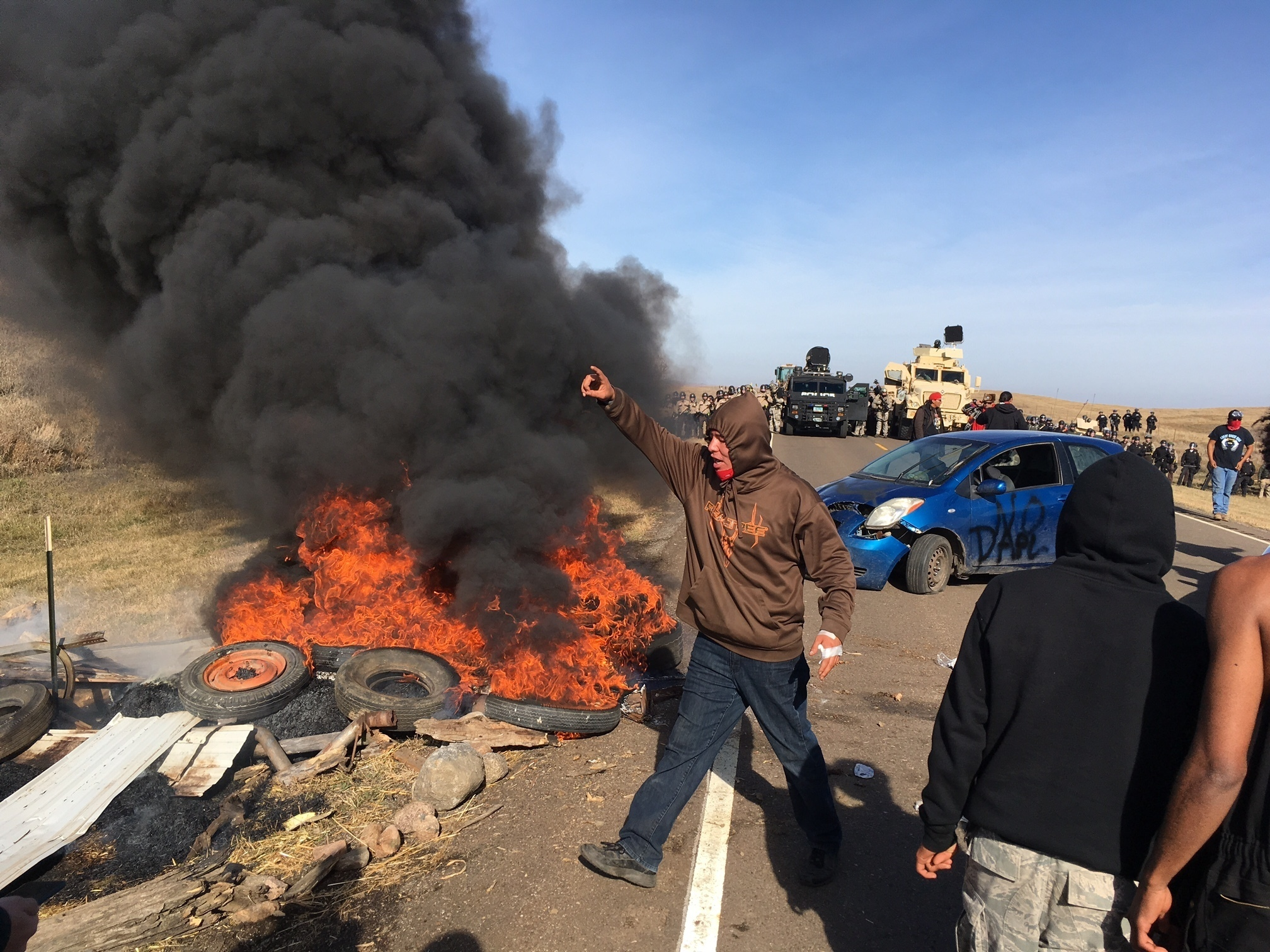 Demonstrators stand next to burning tires as armed soldiers and law enforcement officers assemble on Oct. 27, 2016, to force Dakota Access pipeline protesters off private land where they had camped to block construction. (Mike McCleary/The Bismarck Tribune via AP)