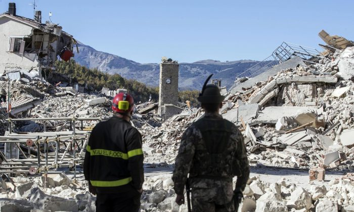 A firefighter (L) and an alpine soldier look at rubble in the hilltop town of Amatrice as an earthquake with a preliminary magnitude of 6.6 struck central Italy, Sunday, Oct. 30, 2016. (Massimo Percossi/ANSA via AP)
