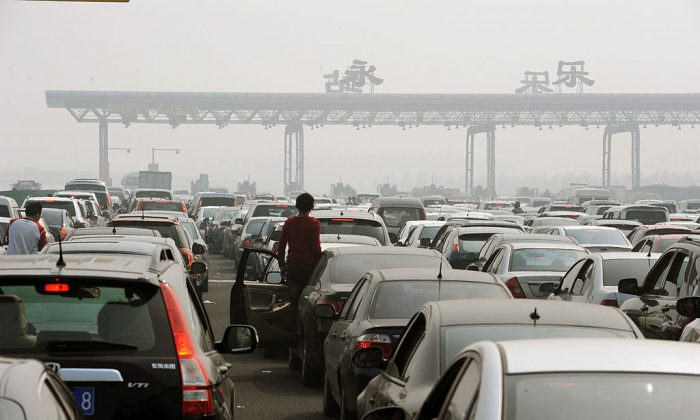 Chinese motorists get out of their cars to check on a massive traffic jam at a toll booth on the outskirts of Beijing on October 2, 2010. (STR/AFP/Getty Images)