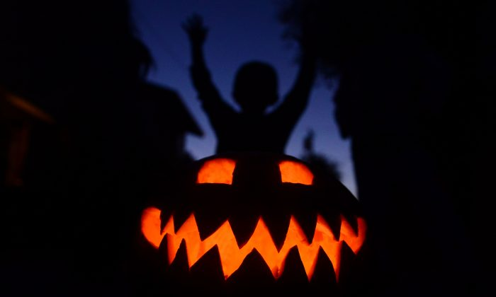 Children play behind a pumpkin carved and lit for Halloween in a file photo. (Frederic J. Brown/AFP/Getty Images)
