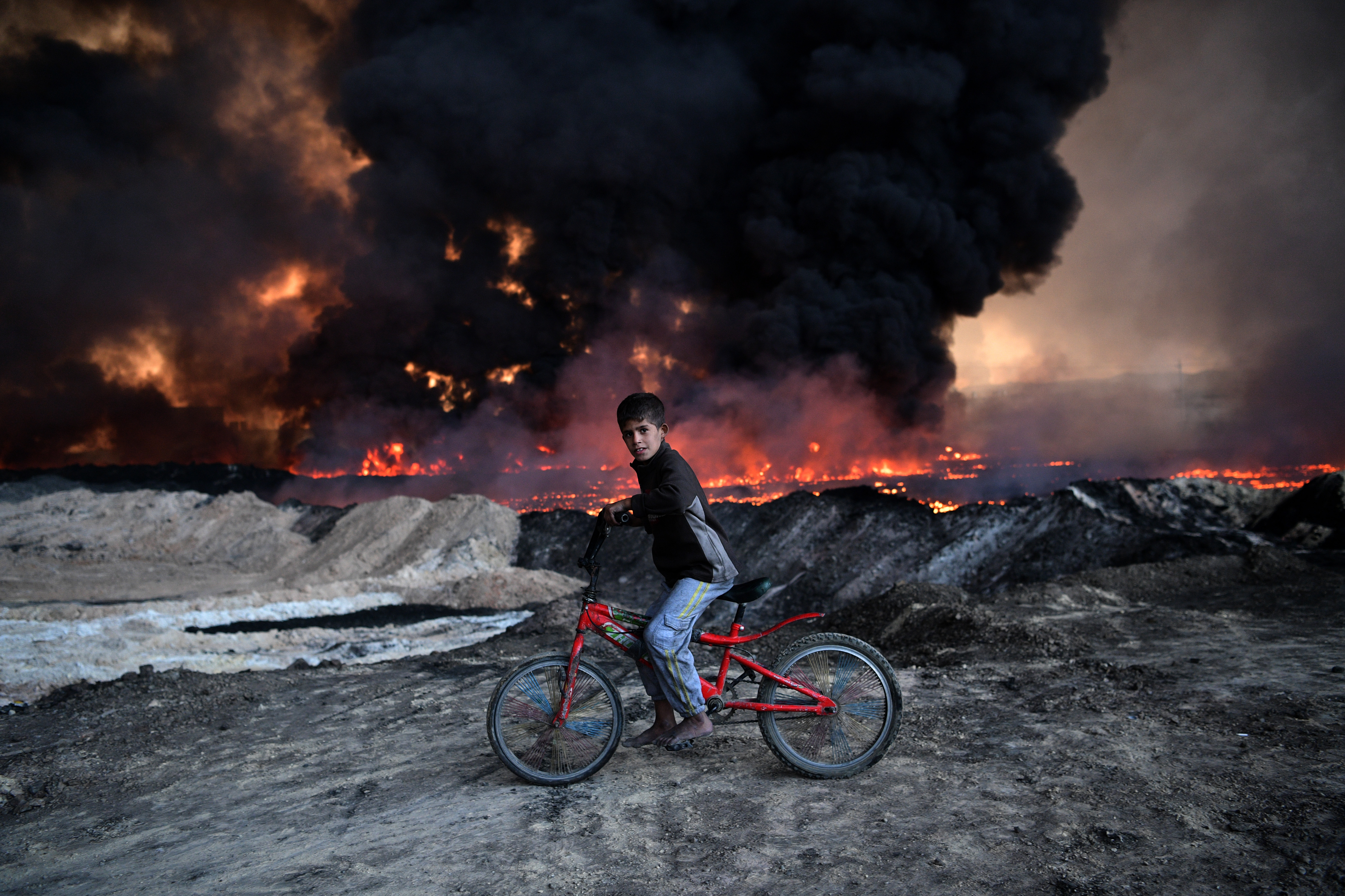 An Iraqi boy passes an oil field that was set on fire by retreating ISIS extremists ahead of the Mosul offensive in Qayyarah, Iraq, on Oct. 21. Several hundred Iraqi families have been made to leave their homes for Mosul by Islamic State fighters as the UN warns they could be used as human shields. (Carl Court/Getty Images)