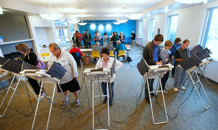 People wait in line and cast their ballots on electronic voting machines on Oct. 25, in Provo, Utah. The GEMS system that counts votes in a quarter of the United States contains code to alter how votes are weighted. (George Frey/Getty Images)