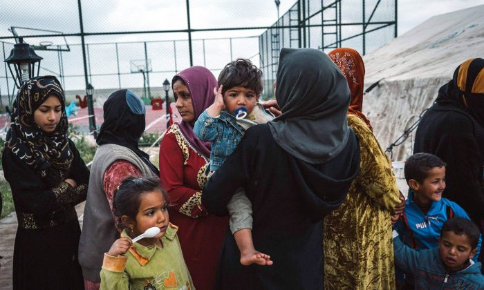 Civilians displaced by heavy fighting between Iraqi security forces and ISIS terrorists wait outside a Doctors Without Borders tent in Makhmour, Iraq, on March 28, 2019. (Alice Martins/Photo via AP)