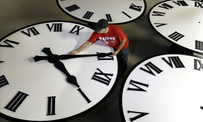Dan LaMoore sizes hands for an 8-foot diameter silhouette clock at Electric Time Co., in Medfield, Mass., on Nov. 4.  Daylight saving time ends at 2 a.m. local time Sunday, when clocks are set forward one hour. (AP Photo/Elise Amendola)