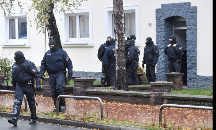 Police officers seach a residential building opposite the German-Speaking Islamic Circle Hildesheim mosque in Hildesheim, Germany, Tuesday, Nov. 8, 2016. German security authorities arrested five men Tuesday on allegations they aided the Islamic State group in Germany, recruiting members and providing financial and logistical help. (JulianStratenschulte/dpa via AP)