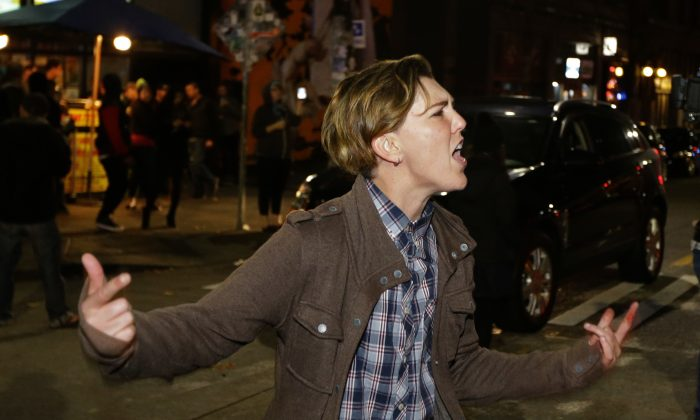 A person yells during a protest against President-elect Donald Trump, Wednesday, Nov. 9, 2016, in Seattle's Capitol Hill neighborhood. (AP Photo/Ted S. Warren)