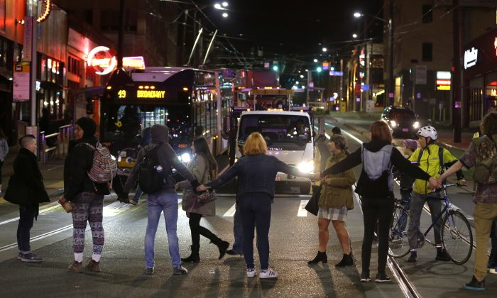 Protesters block a street and stop traffic during a demonstration against President-elect Donald Trump, early Wednesday, Nov. 9, 2016, in Seattle's Capitol Hill neighborhood. (AP Photo/Ted S. Warren)