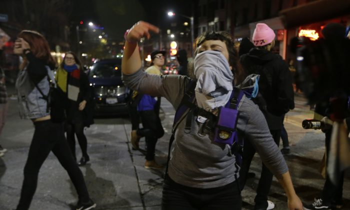 A woman yells as she takes part in a protest against President-elect Donald Trump, Wednesday, Nov. 9, 2016, in Seattle's Capitol Hill neighborhood. (AP Photo/Ted S. Warren)