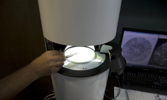Sarine Technologies Ltd. employ puts a diamond in a machine that can instantly grade the clarity of polished diamonds in Ramat Gan, Israel on Nov. 10, 2016. The Israeli high-tech company says the development will bring new standards to a painstaking process that has long been subject to the whims of human subjectivity. (AP Photo/Ariel Schalit)