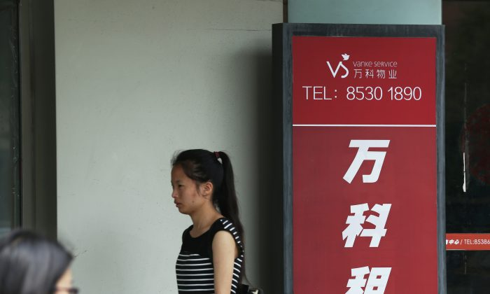 A woman walks past a Vanke Service Center in Beijing July 6, 2016. (STR/AFP/Getty Images)