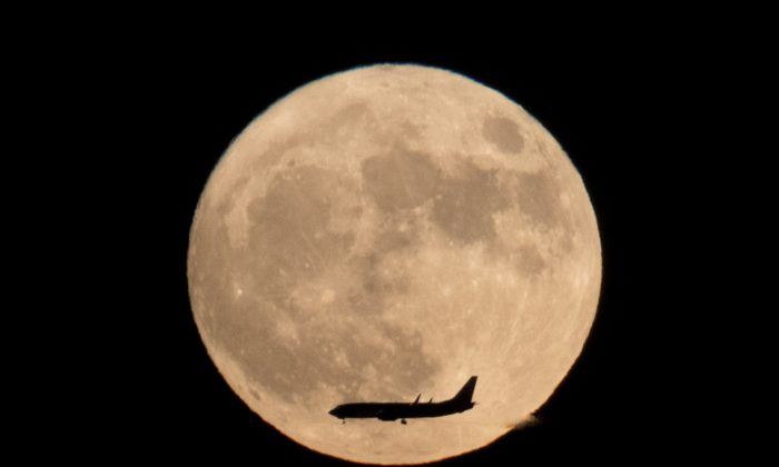 A jet plane flies across the moon seen from Beijing, China, on Nov. 14, 2016. (AP Photo/Ng Han Guan)