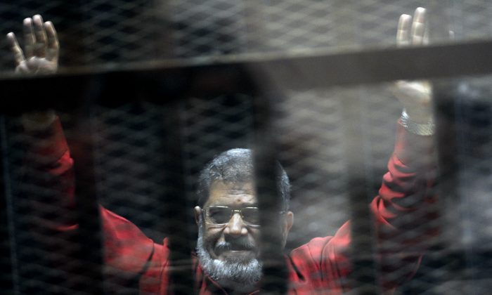 Former Egyptian President Mohammed Morsi, wearing a red jumpsuit that designates he has been sentenced to death, raises his hands inside a defendants cage in a makeshift courtroom at the national police academy, in an eastern suburb of Cairo, Egypt, on  June 21, 2015. (AP Photo/Ahmed Omar, File)