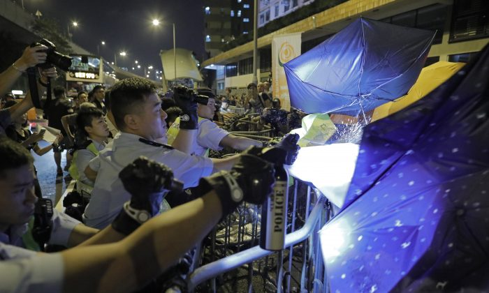 Protesters use umbrellas to block the pepper spray from police officers after clashing outside the Chinese central government's liaison office  after thousands marched in a parade in Hong Kong on Nov. 6, 2016.  (AP Photo/Vincent Yu)