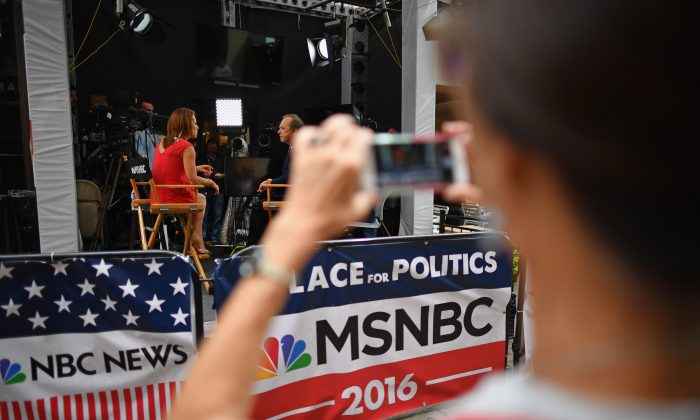 A person photographs an MSNBC news broadcast during the first day of the Republican National Convention in Cleveland, Ohio, on July 18, 2016. (Jeff J Mitchell/Getty Images)
