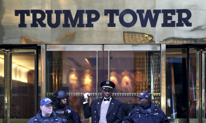 A doorman (C) talks with security personnel at the front entrance of Trump Tower in New York, on Nov. 17, 2016. (AP Photo/Seth Wenig)