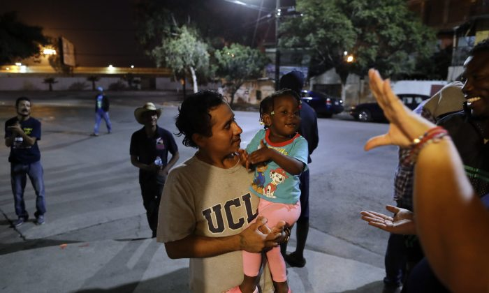 Guatamalan Elvin Vazquez, center, holds a Haitian girl migrating with her family, at a migrant shelter in Tijuana, Mexico, in this file photo. (AP Photo/Gregory Bull)