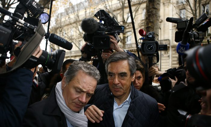 Francois Fillon, right, arrives with his bodyguard at his campaign headquarters in Paris on Nov.21, 2016. Former Prime Ministers Fillon and Alain Juppe will meet in a runoff next Sunday for the nomination to be France's conservative candidate for president. (AP Photo/Francois Mori)