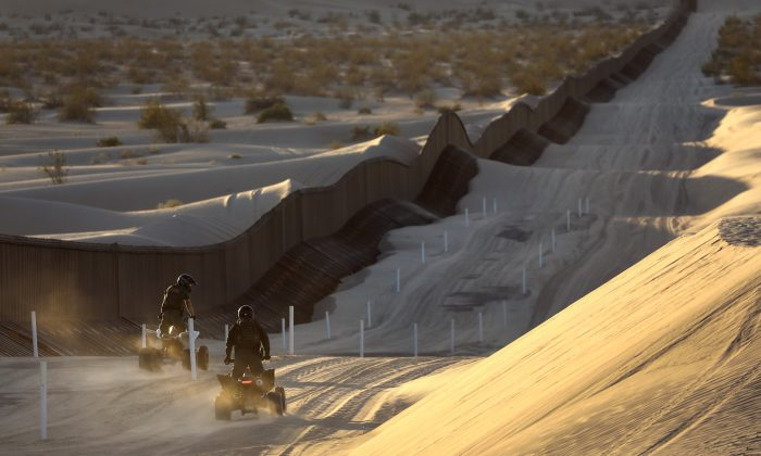 """Border Patrol agents ride ATVs along the U.S.-Mexico border fence at the Imperial Sand Dunes near Felicity, California on Nov. 17, 2016. The 15-foot fence, also known as the """"floating fence,"""" sits atop the dunes and moves with the shifting sands. (John Moore/Getty Images)"""