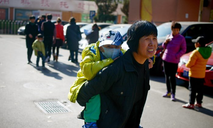 A woman carries a child on her back in Beijing on Nov. 24, 2014. (Wang Zhao/AFP/Getty Images)