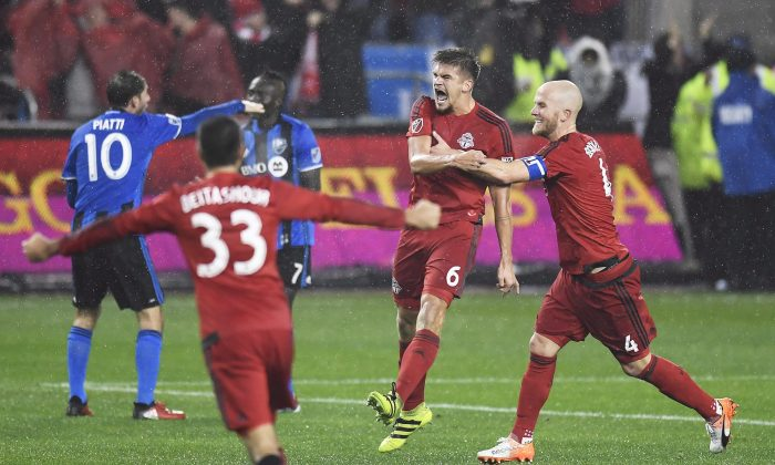 Toronto FC defender Nick Hagglund (6) celebrates his goal against the Montreal Impact with teammates Michael Bradley (4) and Steven Beitashour (33) in Toronto on Nov. 30, 2016. (The Canadian Press/Frank Gunn)