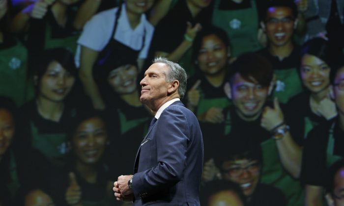 Starbucks CEO Howard Schultz walks in front of a photo of Starbucks baristas, at the coffee company's annual shareholders meeting in Seattle, in this file photo.