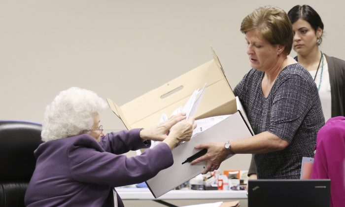 County Clerk Brenda Jaszewski holds a box of absentee ballots from the town of Erin, Wis., as Board of Canvass member Marilyn Merten reaches to take a ballot out during a statewide presidential election recount in West Bend, Wis., on Dec. 1, 2016. (John Ehlke/West Bend Daily News via AP)