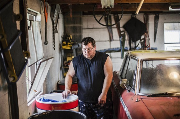 Eric Gilliam, an unemployed coal miner, in his garage at his home in Lynch, Ky., on Oct. 18, 2014. (AP Photo/David Goldman)