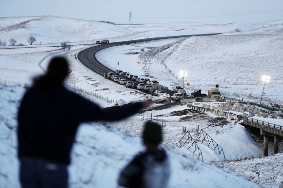 Law enforcement vehicles line a road leading to a blocked bridge next to the Oceti Sakowin camp where people have gathered to protest the Dakota Access oil pipeline in Cannon Ball, N.D., on Dec. 3, 2016. (AP Photo/David Goldman)