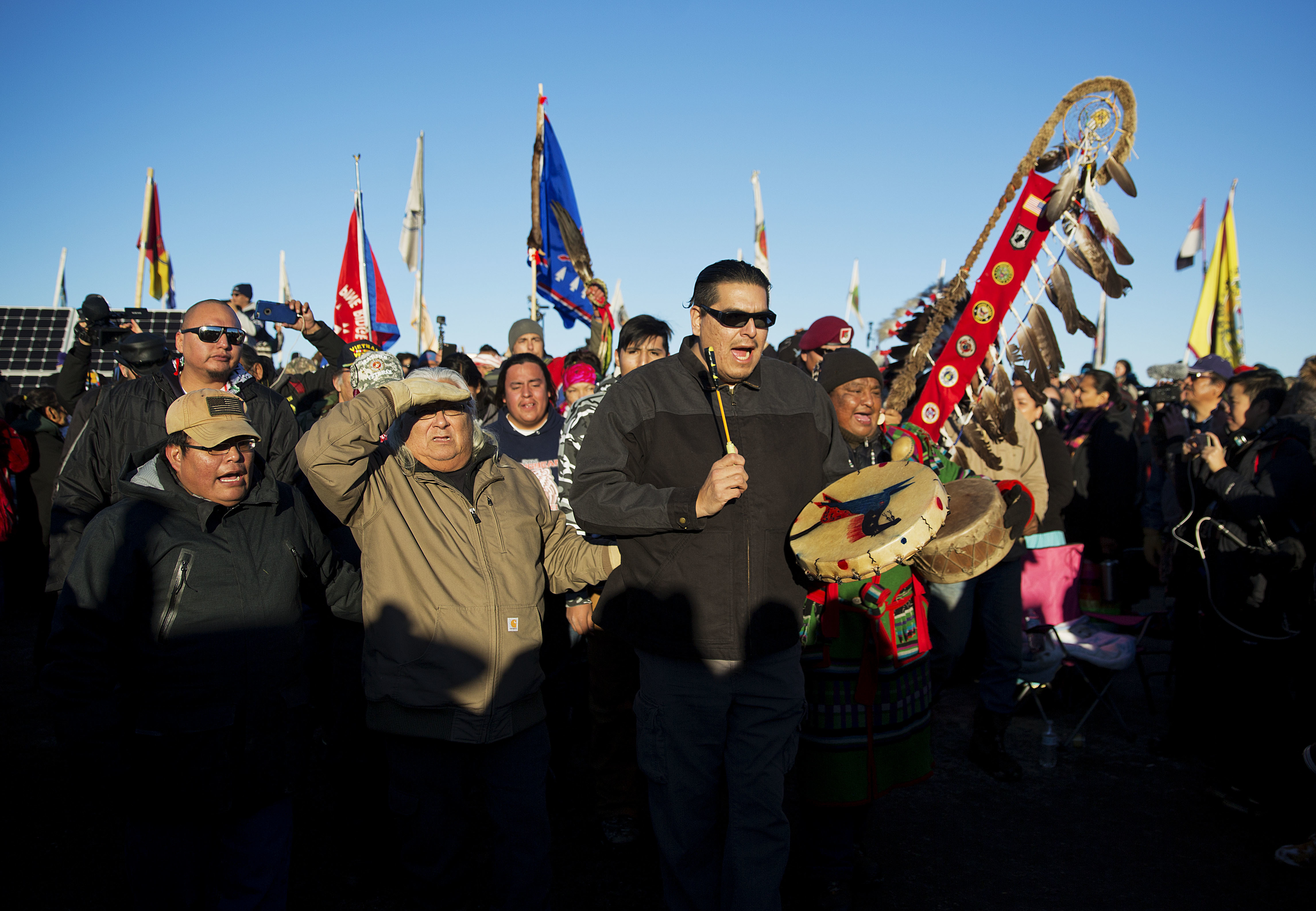 A Native American drum procession moves through the Oceti Sakowin camp after it was announced that the U.S. Army Corps of Engineers won't grant easement for the Dakota Access oil pipeline in Cannon Ball, N.D., on Dec. 4, 2016. (AP Photo/David Goldman)