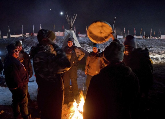 Campers gather around a fire to sing and drum traditional Native American social songs at the Oceti Sakowin camp where people have gathered to protest the Dakota Access oil pipeline in Cannon Ball, N.D., on Dec. 4, 2016. (AP Photo/David Goldman)