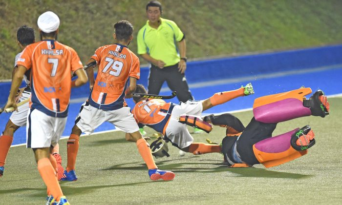 Khalsa-A's Inderpal Singh falls as the SSSC-A goalie dashes from his goal to stop the attack. A penalty stroke was awarded from which Khalsa reduced the deficit to 2-3, in their HKHA Premier Division match at King's Park on Sunday Dec 4.  The match ended 3-3.(Bill Cox/Epoch Times)