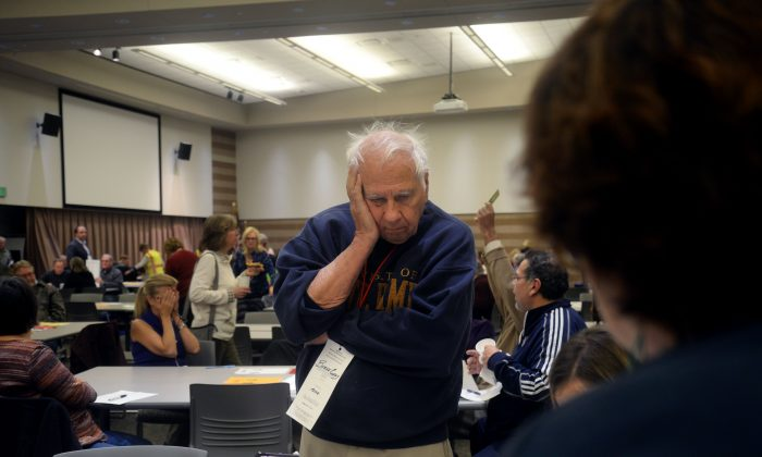 Burke Cueny, of Rochester, watches as volunteers and city officials participate in a recount after a federal judge ordered the statewide recount at the Oakland Schools Conference Center in Waterford Township, Michigan on Dec. 5, 2016. (Rachel Woolf/Getty Images)