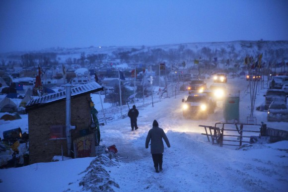 A motorist checks the condition of an exit ramp before attempting to drive out of the Oceti Sakowin camp where people have gathered to protest the Dakota Access oil pipeline in Cannon Ball, N.D. on Dec. 6, 2016. An overnight storm brought several inches of snow, winds gusting to 50 mph and temperatures that felt as cold as 10 degrees below zero. (AP Photo/David Goldman)