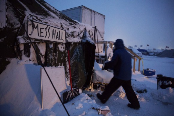 Ray Franks, of New York, carries a case of water into a mess hall at the Oceti Sakowin camp where people have gathered to protest the Dakota Access oil pipeline in Cannon Ball, N.D. on Dec. 6, 2016. An overnight storm brought several inches of snow, winds gusting to 50 mph and temperatures that felt as cold as 10 degrees below zero. (AP Photo/David Goldman)