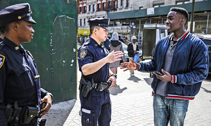 Police officers Max Chow (C) and Shakara President greet a pedestrian on 125th Street in Harlem, New York, on April 29, 2015. (AP Photo/Seth Wenig)