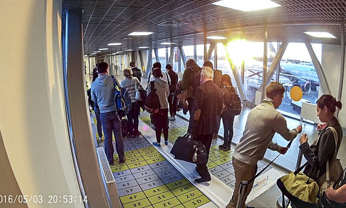 Passengers take their places on the Flying Carpet boarding system during its very first trial on a flight at Pulkovo Airport in St. Petersburg, Russia in which 171 passengers boarded an Airbus A321 in 13 minutes. (Vlad Kolesnik)