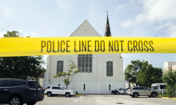 Police tape surrounds the parking lot behind the AME Emanuel Church as FBI forensic experts work the crime scene, in Charleston, S.C.  (AP Photo/Stephen B. Morton)