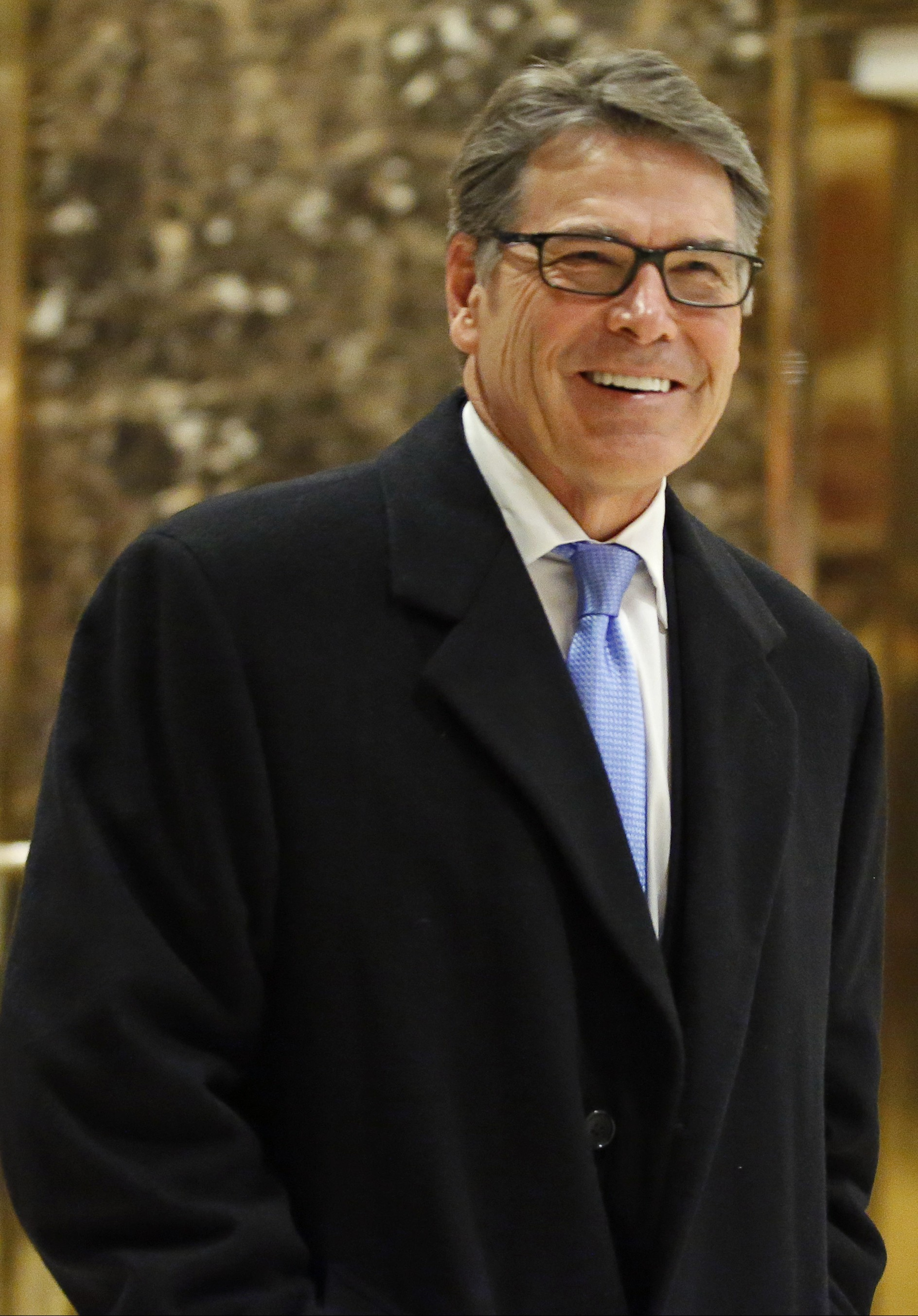 Former Texas Gov. Rick Perry smiles as he leaves Trump Tower in New York on Dec. 12, 2016. (AP Photo/Kathy Willens)