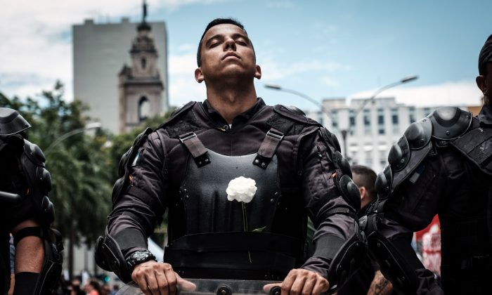 A riot police officer bearing a white flower on his bulletproof vest in Rio de Janeiro, Brazil, on Dec. 12, 2018. (Yasuyoshi Chiba/AFP/Getty Images)