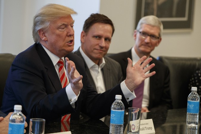 Apple CEO Tim Cook (R) and PayPal founder Peter Thiel (C) listen as President-elect Donald Trump speaks during a meeting with technology industry leaders at Trump Tower in New York on Dec. 14, 2016. (AP Photo/Evan Vucci)