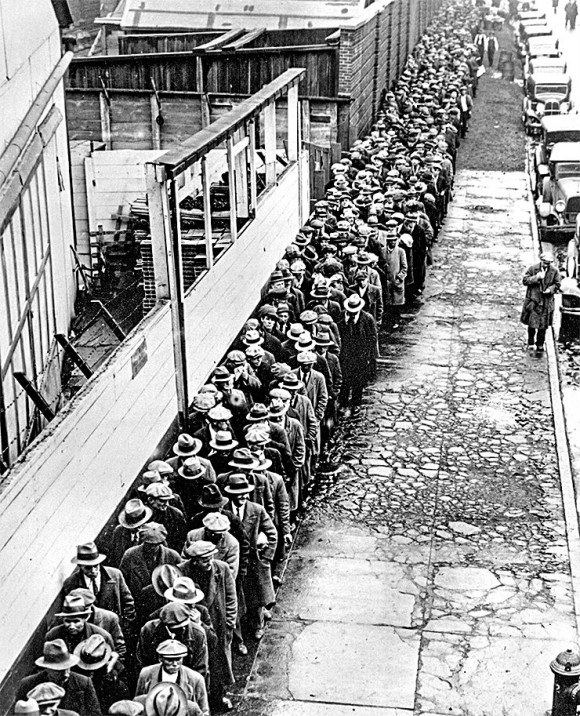 Jobless and homeless men wait to get free dinner at New York's municipal lodging house in the winter of 1932–33. Companies and banks defaulted in droves during the Great Depression because of too much debt, causing a crash in GDP and massive unemployment.
