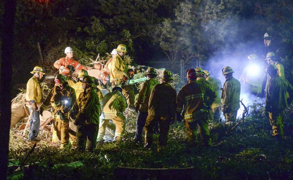 Los Angeles County Fire Dept. firefighters work at the scene where a large tree fell on a wedding party in Whittier, Calif., on, Dec. 17, 2016. (Keith Durflinger/The Whittier Daily News via AP)
