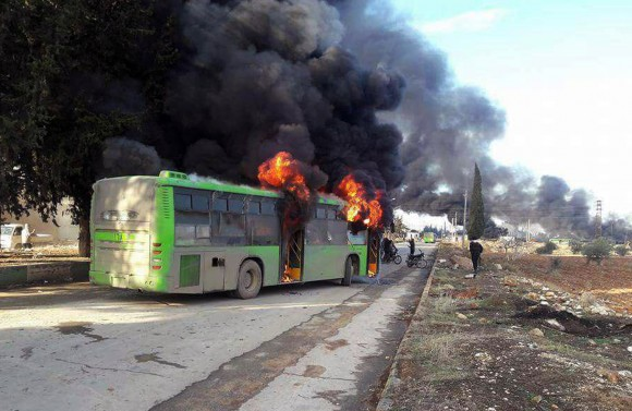 In this photo released by the Syrian official news agency SANA, smoke rises in green government buses, in Idlib province, Syria on Dec. 18, 2016. (SANA via AP)