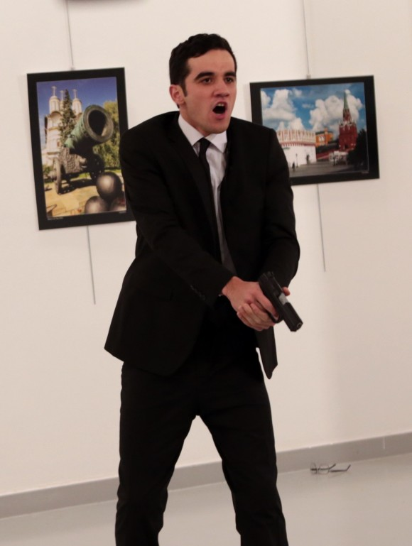 A man identified as Mevlut Mert Altintas holds up a gun after shooting Andrei Karlov, the Russian Ambassador to Turkey, at a photo gallery in Ankara, on Dec. 19, 2016.