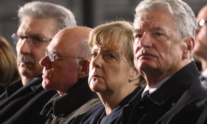 (R-L) German President Joachim Gauck, Chancellor Angela Merkel and the President of the German Parliament, Norbert Lammert, and other politicians attend a memorial service in Berlin's Kaiser-Wilhelm Memorial Church for the victims of a truck attack on a crowded Christmas market the day before, killing several people on Dec. 20, 2016. ( Michael Kappeler/Pool Photo via AP)