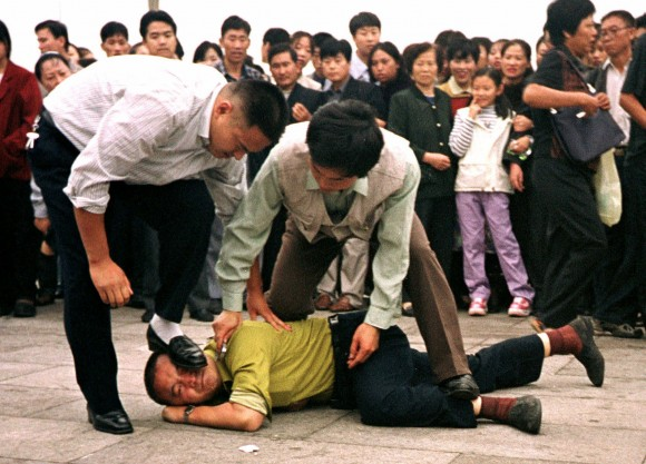 Police detain a Falun Gong protester in Tiananmen Square on Oct. 1, 2000. In 2016—the 17th year of the Chinese regime's persecution of Falun Gong-mass arrests continue, but Chinese officials in parts of the country have started declining to press charges against arrested practitioners. (AP Photo/Chien-min Chung)