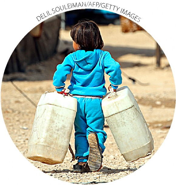 A girl carries water tanks in a refugee camp in Syria's Hasakah Province on Oct. 25.